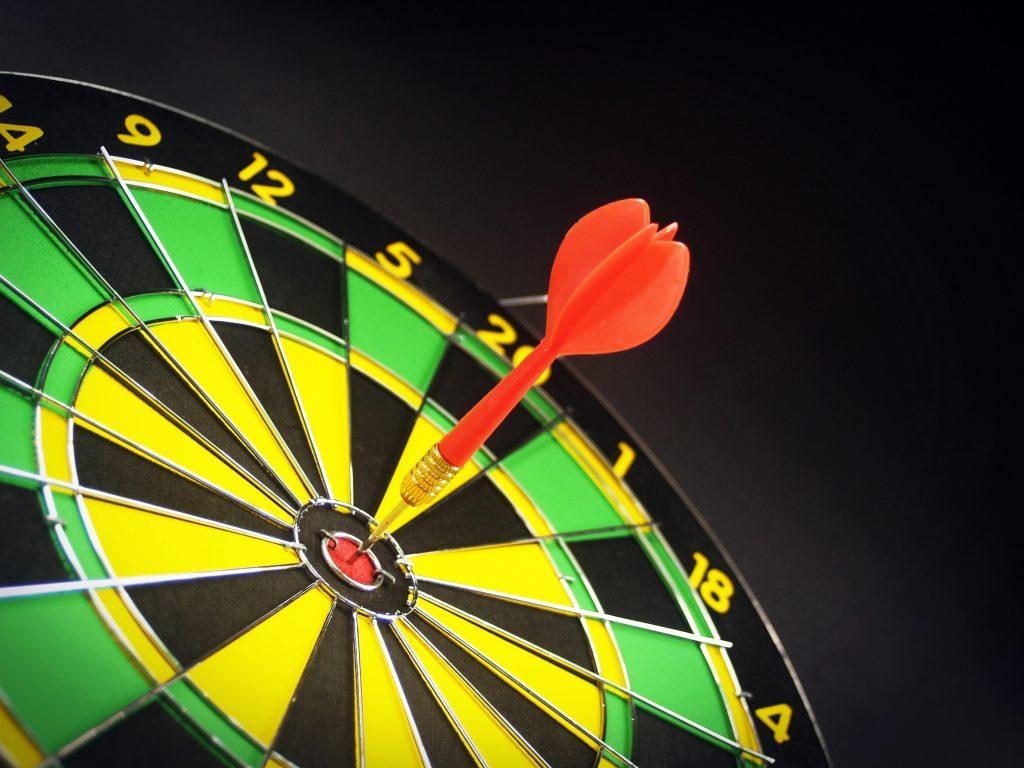 Orange dart hitting a bullseye on a dart board