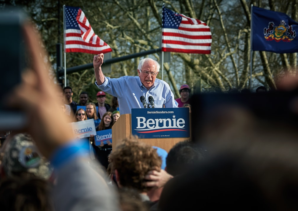 Bernie Sanders at a rally with flags in background