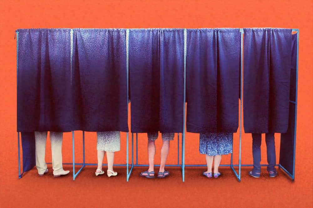 Voter booth with people's feet shown on a dark background