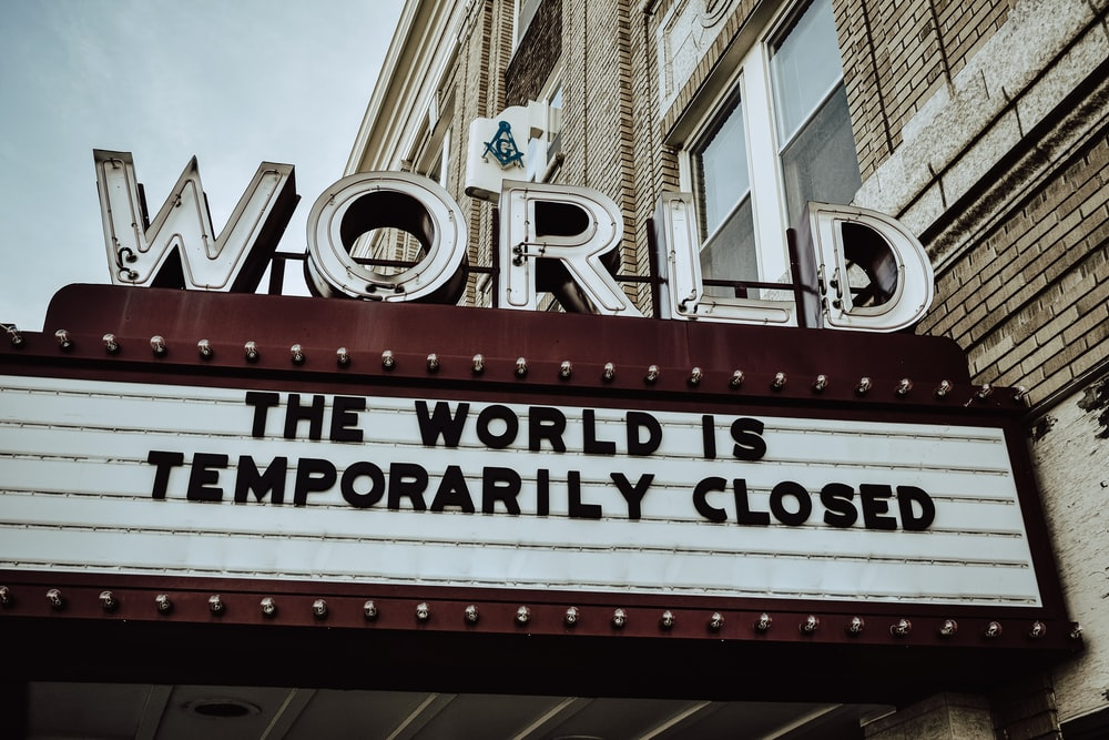 "Movie Theater Sign with the words ""The World is Temporarily Closed"" displayed"