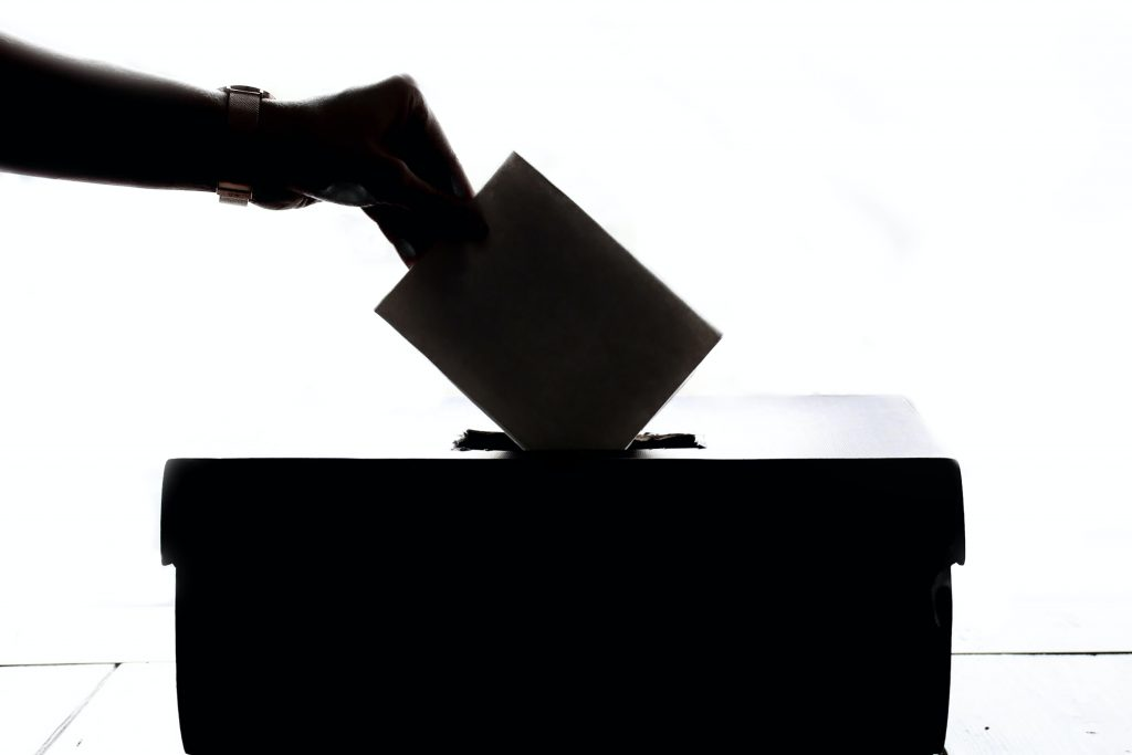 Black and white picture of a ballot going into a ballot box