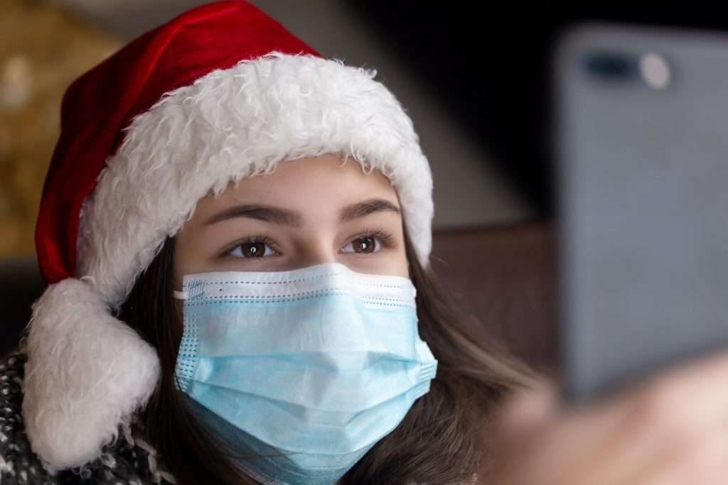 Woman wearing a santa hat and also a face mask