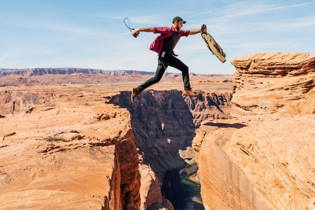 Man in baseball hat jumping from one ledge to another in a canyon