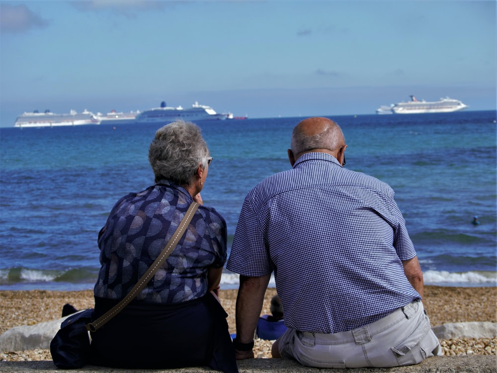 An elderly couple sitting on the beach looking out into the ocean