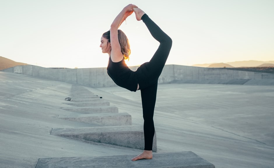 Woman in black outfit doing a yoga pose