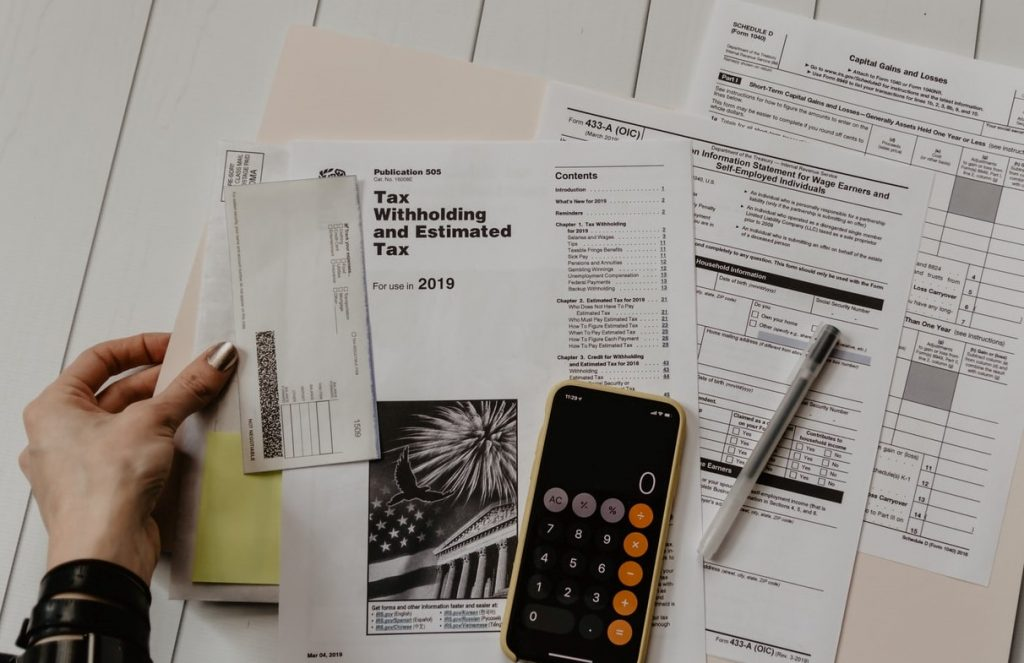 Tax forms on a table with a phone and pen on the forms