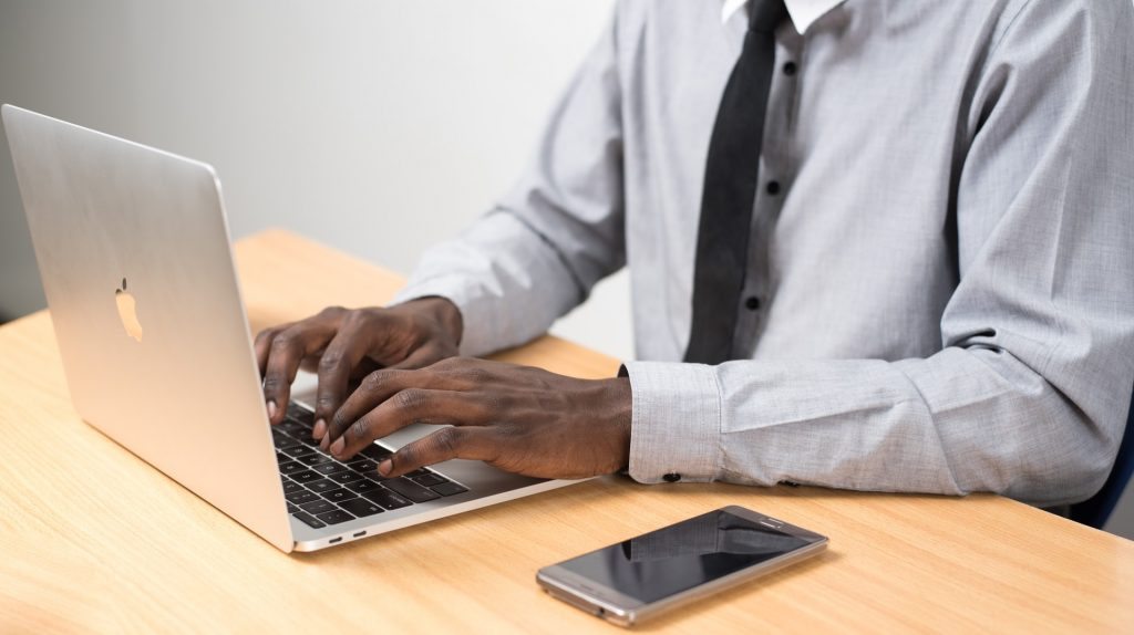 Two hands typing on a computer with a phone next to the computer