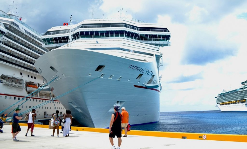 Cruise ship docked in a port with people walking by
