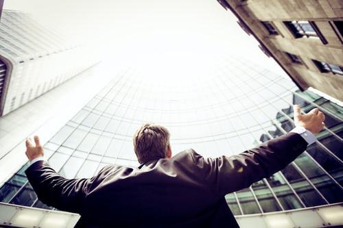 Person with their arms spread out looking up at city buildings